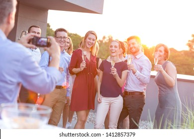 Businessman photographing colleagues during rooftop success party