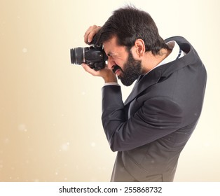 Businessman photographing over ocher background