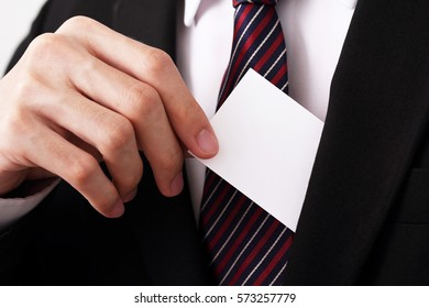 businessman picking up blank white card from pocket inside suit