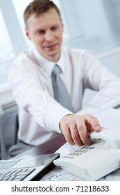 Businessman picking up telephone receiver