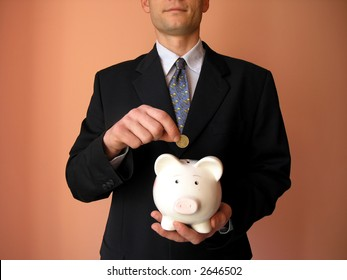 Businessman with a piggy bank.He puts coin in a piggy bank.