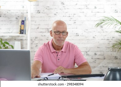 a businessman with a pink polo shirt works in his office