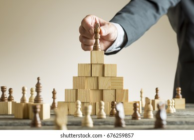 Businessman placing a chess piece on a pyramid of wooden building blocks in a concept of success and achievement in a close up view of his arm.