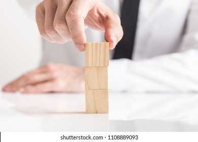 Businessman placing empty wooden blocks on top of each other, viewed in close-up against white background.