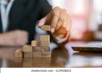 Businessman planing and strategy putting wooden blocks risk or success project hands control stack of danger tower challenge game building construction protect at office.