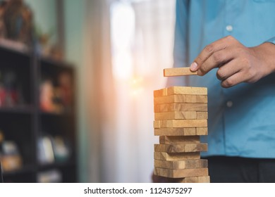 Businessman planing and strategy putting wooden blocks risk or success project stack of danger tower hands playing challenge game building construction protect at office.