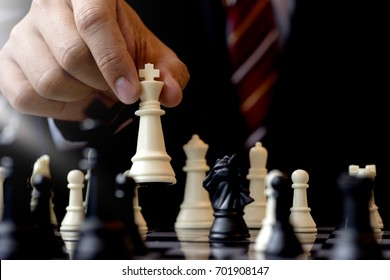 Businessman play chess use King Chess Piece white to crash overthrow the competitor concept business strategy for win
