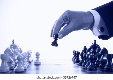 businessman playing chess game blue tone selective focus