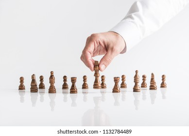 Businessman playing chess moving dark king piece lifting it up in his fingers on white table.