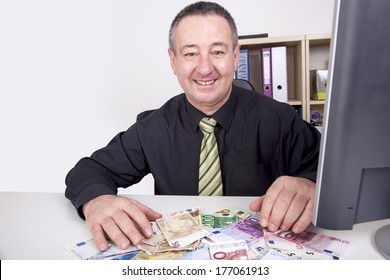 Businessman is pleased with his money on the desk