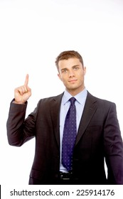 Businessman pointing above his head towards blank while copyspace while looking at the camera with a serious expression