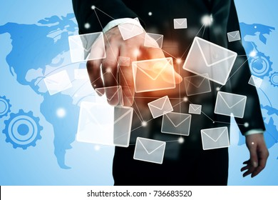 Businessman pointing at abstract glowing letters on map background. E-mail networking concept. Double exposure