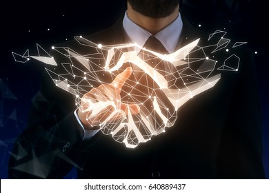 Businessman pointing at abstract polygonal handshake on dark background. Team concept