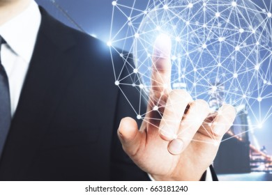 Businessman pointing at abstract polygonal sphere on city background. Tech concept
