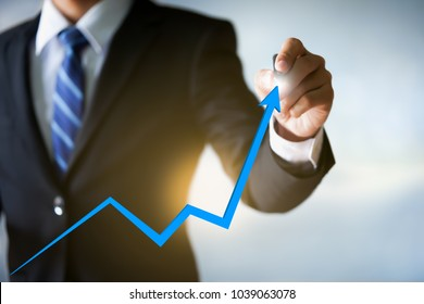Businessman pointing arrow graph, business analytics and financial technology concept.