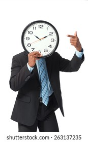 Businessman pointing at the big clock in front of his face: deadline concept