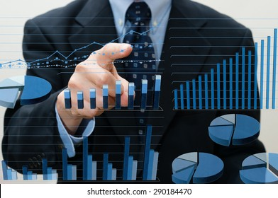 Businessman pointing business charts projected on the transparent screen