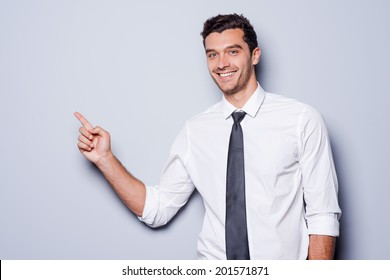 Businessman pointing copy space. Happy young man in shirt and tie looking at camera and smiling while standing against grey background and pointing copy space