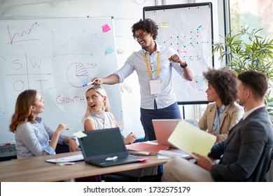 Businessman pointing at a coworker in a pitch meeting.  Coworkers discussing in a meeting. Great team work example.