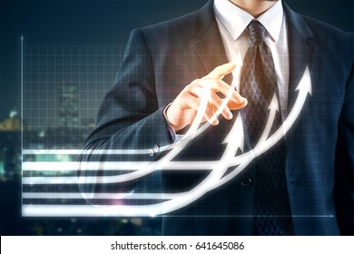 Businessman pointing at creative business chart with upward arrows on night city background. Financial growth concept