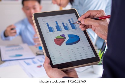 businessman pointing to the data on the tablet. The business team of the organization is brainstorming with charts and examining and analyzing the company's marketing and investments in the future.
