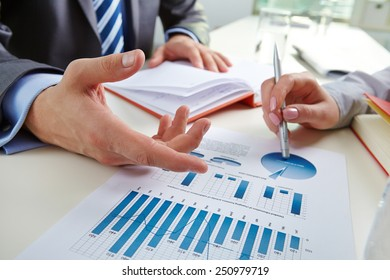 Businessman pointing at document with chart during discussion with colleague