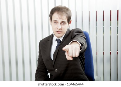 Businessman pointing a finger singling out a specific person to delegate work or to lay blame, indicating his choice or identifying somebody
