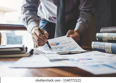 Businessman pointing at graph and chart to analysis use for plans to improve quality, business finances and accounting concept.