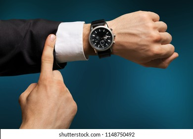 Businessman pointing at hand watch