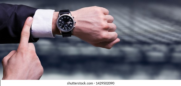 Businessman pointing at hand watch on grey
