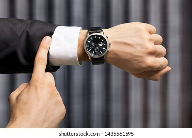 Businessman pointing at hand watch on grey wall background, close-up
