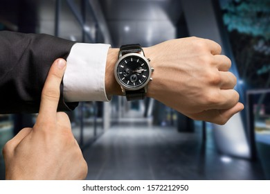 Businessman pointing at hand watch on grey wall background