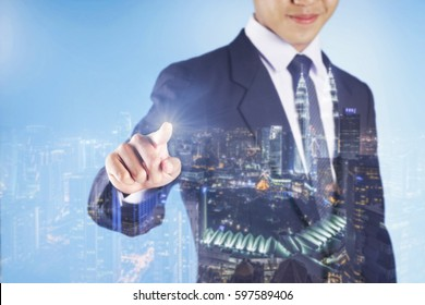 Businessman pointing his finger into the touch screen with cityscape background - Double exposure