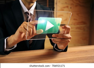 businessman pointing at a movie playback button.