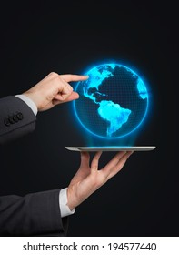 Businessman pointing out the digital globe. Elements of this image furnished by NASA.