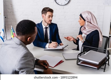 businessman pointing with pen at contract near arabian businesswoman and interpreter, blurred foreground