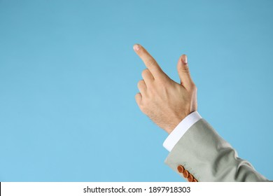 Businessman pointing at something on light blue background, closeup. Finger gesture