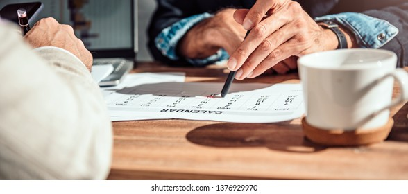 Businessman pointing to a specific date on a calendar during a meeting in the office