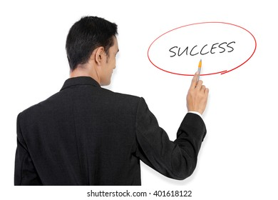 """Businessman pointing at """"Success"""" handwritten text on white board with his pen"""