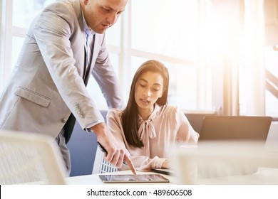 Businessman pointing at tablet on table with female colleague paying attention to his instructions as he supervises her work and provides guidance to help her.