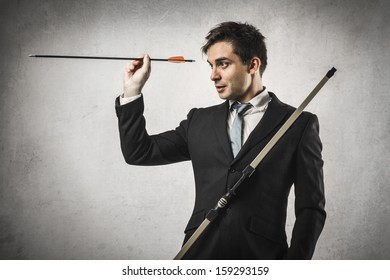 businessman pointing the target with bow and arrow