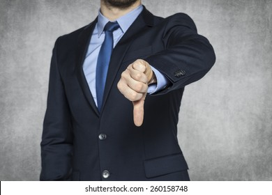 Businessman pointing thumbs down