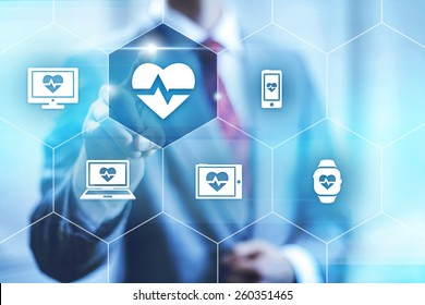 Businessman pointing towards camera selecting health application, virtual interface