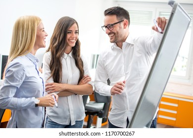 Businessman pointing using marker to flipboard during presentation with colleagues in office