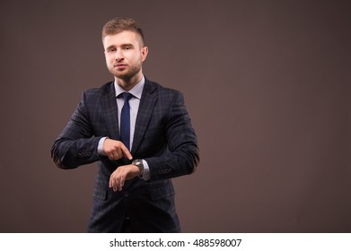 Businessman pointing to watch and grins