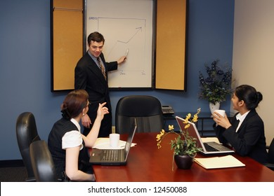 Businessman pointing to the whiteboard as he presents to two female colleagues during a meeting