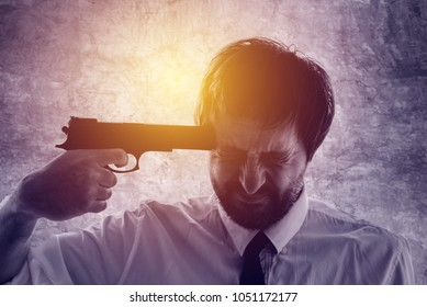 Businessman points gun to his head, disappointed suicidal man about to commit a suicide. Unemployment and business failure concept, ultra violet toned shadows