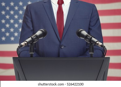 Businessman or politician making speech from behind the pulpit with USA flag on background