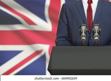 Businessman or politician making speech from behind the pulpit with national flag on background - United Kingdom
