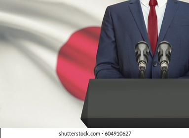 Businessman or politician making speech from behind the pulpit with national flag on background - Japan